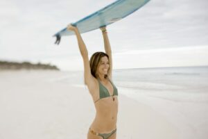 Woman carrying surfboard on beach